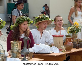 31.8.2018, Trnava, Slovakia Women in costumes sitting at a wooden table with wine containers. The picture comes from a medieval grape press, which takes place in the courtyard of the town hall.