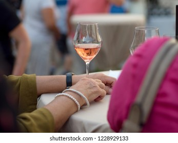 31.august 2018, Trnava, Slovakia The female hand with pearl bracelets holds a cup of pink rose wine. It reflects the surrounding buildings.