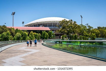 31st December 2018, Adelaide South Australia : People on riverbank curved footbridge over torrens river and Adelaide Oval stadium in background in Adelaide SA Australia