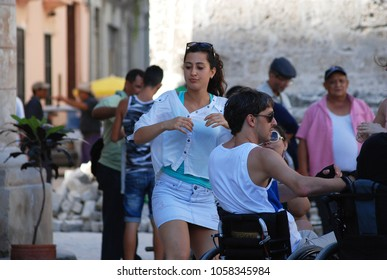 31st of October 2013 - Scene from Plaza de la Catedral (Cathedral Square) with young woman dancing  with man in a wheelchair,  Havana, Cuba