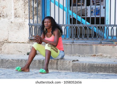 31st of October 2013 - Scene from Plaza de la Catedral (Cathedral Square) with young woman sitting on a granite curb hiding her face in front of a metal grid, Havana, Cuba