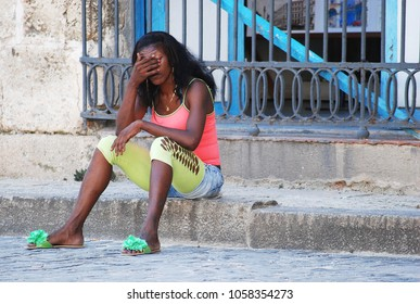 31st of October 2013 - Scene from Plaza de la Catedral (Cathedral Square) with young woman sitting on a granite curb in front of am etal grid her hand before her eyes, Havana, Cuba