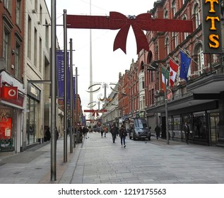 31st October 2018 Dublin. Christmas street decorations on Henry Street, one of Dublin's main shopping streets, including a large red ribbon bow, with the Dublin Spire in the background.
