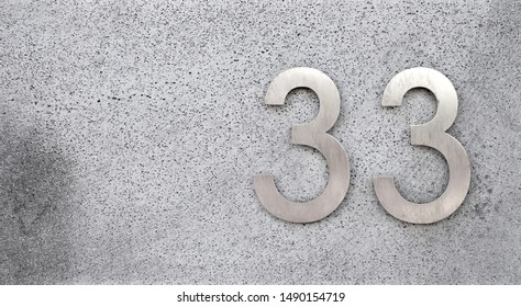33, number thirty-three, elegant silver metalic digits on gray surface, offset with copy space.