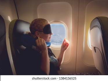 33 year old woman using traveling pillow, sleeping mask and ear plugs in plane cabin on passenger seat, fly with airplane, comfortable cozy traveling concept.