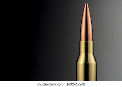 A 338 Lapua Magnum rifle cartridge in front of a gray gradient as a close-up. Brass and copper stand against the background like a monumental building. Even a dangerous object has its own aesthetic