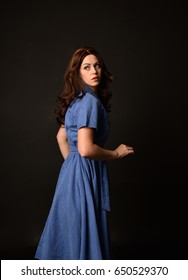 3/4 portrait of a brunette girl wearing a vintage blue dress again a black studio backdrop.