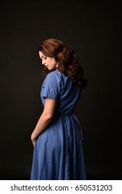 3/4 portrait of a brunette girl wearing a vintage blue dress again a black studio backdrop.
