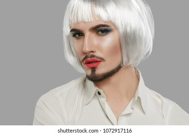 3/4 view portrait of a male beauty blogger in a button-up shirt, wearing green eye makeup, neat goatee, silver bob wig, neck tattoo. The feminine guy looking at the camera, his lips slightly parted.