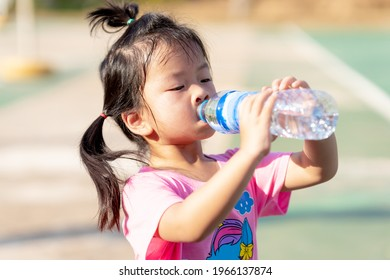 A 3-4 years old girl was drinking water to quench her thirst due to the hot weather. Kid sweat on their faces. Child drink cold water. Cute children wearing a pink shirt. In the summer or spring.
