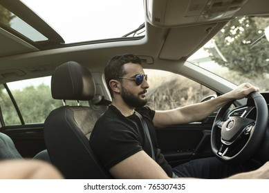 35 years old man driving his car with sunglasses in afternoon trip