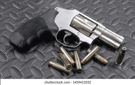 357 Magnum J-frame Revolver and jacketed hollow-point bullets on black rubber floor