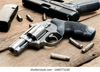 .357 magnum revolver, 9mm pistol, bullets and, magazines on wooden table
