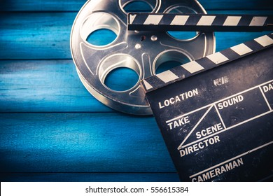 35mm film reel and movie clapper with dramatic lighting on a wooden background
