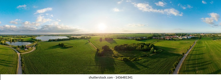 360 degree spherical panorama of green agricultural fields with a lake and a small town in the background in the golden evening sun - aerial view - drone