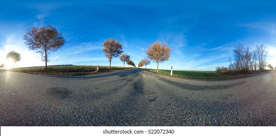 360 degrees spherical panorama of a asphalt country road with trees at late afternoon in autumn - germany