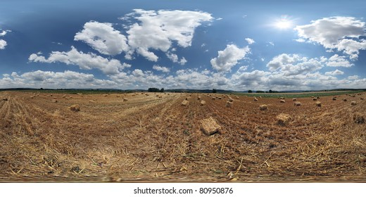360 VR panorama  Beautiful summer sky over freshly harvested wheat field, littered with small cubical hay bales  NOTE: its not banding in the sky, those are sun rays clearly visible in VR
