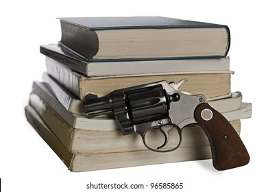 A .38 caliber pistol stands in front of school textbooks, isolated on white, focus on gun handle