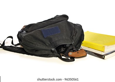A 38 caliber pistol sticks out from a child's school book-bag in front of school textbooks, isolated on white, focus on gun handle