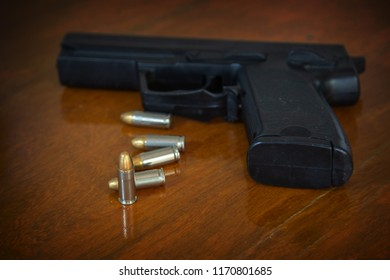 .38 mm handgun and bullets strewn on the rustic wooden table background. Gun with ammunition on wooden background and Isolated Gun and ammo.