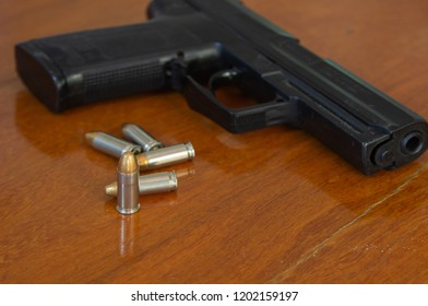 .38 mm handgun and bullets strewn on the rustic wooden table background. Gun with ammunition and isolated ammo or 9mm handgun on wood surface at home. Protect property refers to serious social issues