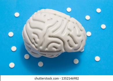 3D anatomical model of brain is on blue background surrounded by white pills as ornament polka dots. Medical concept by pharmacological tablet treating brain diseases, pharmacotherapy, chemotherapy