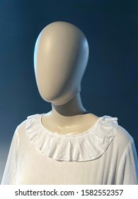 3D dummy photo of woman mannequin in a white dress with a collar with studio light, blue and white in front of dark blue wall