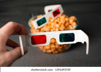 3D glasses and cheesy popcorn lie at night in a glass plate on a gray bed, a person puts on glasses
