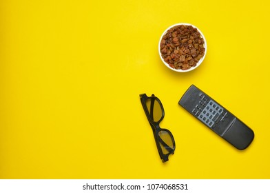 3d glasses, tv remote,  bowl with raisins on a yellow background, top view