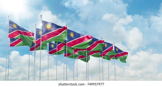 3d illustration of many flags of Namibia in rows waving in the wind against blue sky