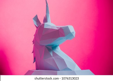 3D paper unicorn on pink background left side, horizontal. Origami toy. Origami pegasus