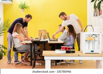 3D printer machine with products on counter with designers working in background at creative studio