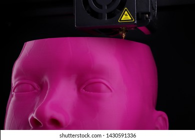 3D printer manufacturing a humanoid head from pink plastic - detailed closeup on forehead with visible layer and print head - futuristic and technology concept
