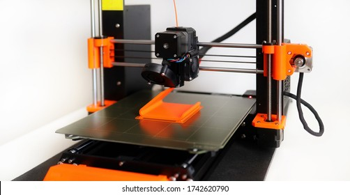 3D Printer in operation with orange filament on a white background - FFF (Fused Filament Fabrication) or FDM (Fused Deposition Modelling). Home 3D open-source DIY printer