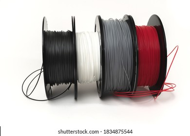 3D Printer Plastic Filament. Spools of black, red, grey, white thermoplastic wires  for 3d printing close up isolated on white background