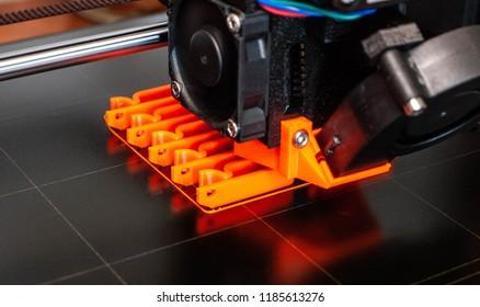3D printer printing bright orange clips on a black bed.