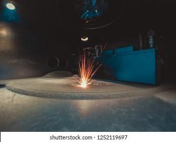 3D printer printing metal. Laser sintering machine for metal. Metal is sintered under the action of laser into shape. DMLS, SLM, SLS. Modern additive technologies 4.0 industrial revolution. Sparks
