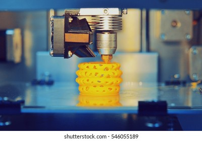 3d printer printing objects yellow form closeup. Modern technical 3D printing.