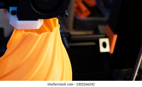 3D printer printing an orange vase with a dark background.