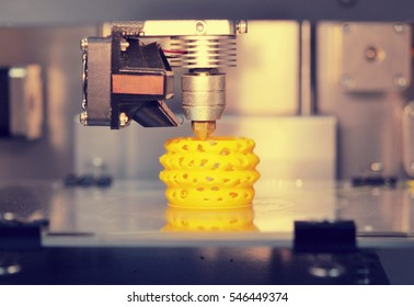 3D printer prints from the plastic figure closeup. 3D printer makes yellow model close-up on gray flat surface