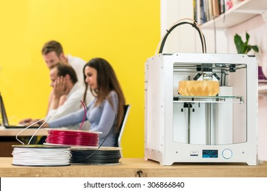 A 3D Printer and some coils with biodegradable polymer string on a table in front of a group of designers, at work behind computers and laptops