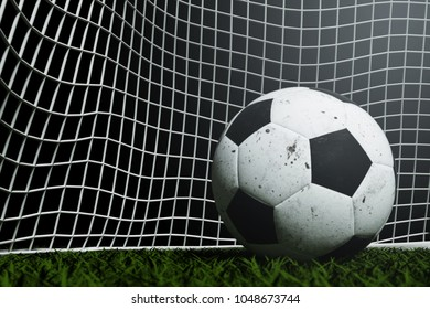 3D Rendering : illustration of a soccer ball on green grass. white and black leather. texture of ball with dark background. high-resolution. white metal goals at background. business goals concept