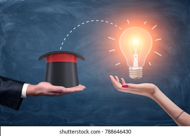 3d rendering of a male businessman's hand holding a wizards hat and a female hand holding a bright glowing lamp. Corporate magic. Business ideas. Beneficial partnership.