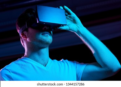 3d technology, virtual reality, entertainment and people concept - young man in vr glasses playing game over ultra violet neon lights in dark room