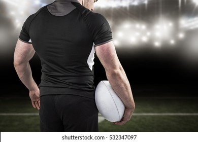 3D Tough rugby player holding ball against american football arena