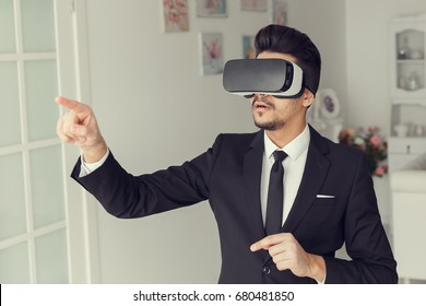 3d vision technology concept, video simulation. Young man in suit and virtual glasses. Digital vr device