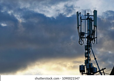 3G, 4G and 5G cellular. Base Station or Base Transceiver Station. Telecommunication tower. Wireless Communication Antenna Transmitter agaisnt sunset with dark clouds.