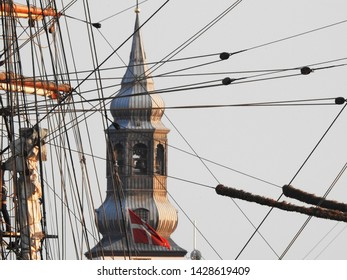 3rd of August 2015  - Details form a vintage tallship with view past rigging to a blurred tower of the Cathedral, Aalborg, Denmark