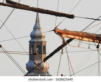 3rd of August 2015  - Details from a vintage tallship with view past rigging tand yards to a blurred tower of the Cathedral, Aalborg, Denmark