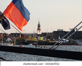 3rd of August 2015 - Scene from a Danish harbor with view past a blurred Russian flag and a bridge to a skyline, Aalborg, Denmark